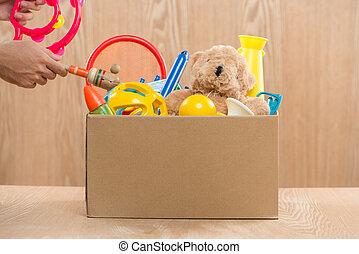 macho, voluntário, segurando, caixa donation, com, antigas, toys.