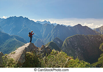 Man with camera on peak of mountain