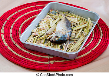 Mackerel fish on a grill with lemongrass