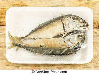 mackerel steamed in foam white tray on wooden background