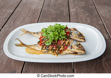 Mackerel with chili sauce in a white tiled plate on a wooden table.