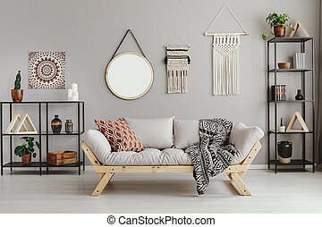 Macrame, mirror and ethno graphic on beige wall in stylish ...