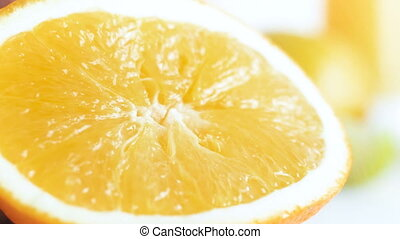 Macro 4k footage of fresh orange being squeezed on white...