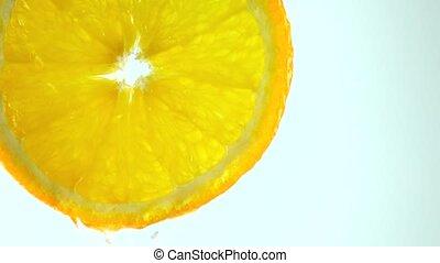 Macro 4K video of orange slice and draining water against...
