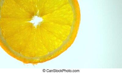 Macro 4K video of orange slice and dripping water against...