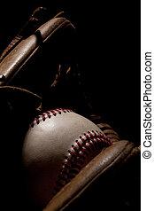 Macro Baseball and Glove on Black Background - Macro shot of...