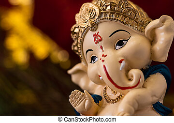 macro close up of beautiful ganesha statue in blessing pose against blurred red and golden background. religion and hindu concept.