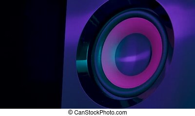 Macro close up of black vibrating membranes loud sound speaker in colorful neon lighting. Close up. Slow motion