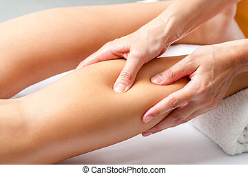 Hands applying pressure with fingers on calf muscle. - Macro...
