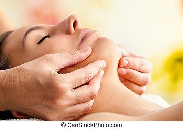 Hands massaging female chin.