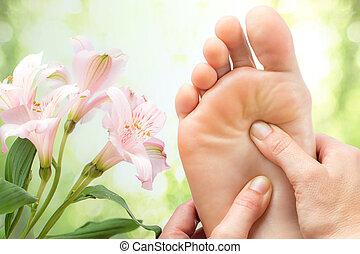 Macro detail of foot massage next to flowers. - Macro close...