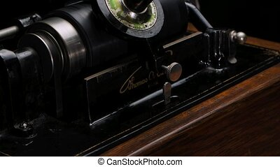 Macro detailed filming Classic Edison Phonograph plays music on a black studio background. Retro vintage machine to reproduce sound making listening to music. Close up. Slow motion