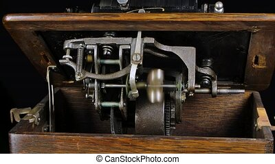 Macro detailed shot of the internal mechanisms of a classic phonograph on a black studio background. Rotating parts of a retro musical instrument. Close up. Slow motion