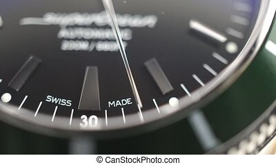 Macro dolly shot of second hand of luxury swiss made watch with green bezel