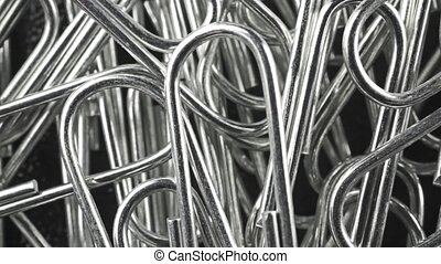 Macro dolly shot of steel paper clips, view from above clip