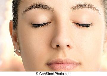 Macro face shot of woman meditating with eyes closed.