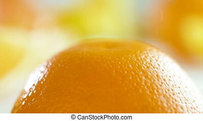 Macro footage of water droplets falling on orange peel -...