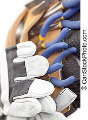 macro image of a tool belt and hand gloves