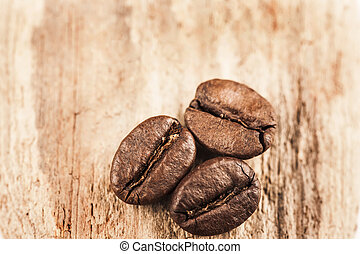 Macro image of coffee beans on wooden surface close up
