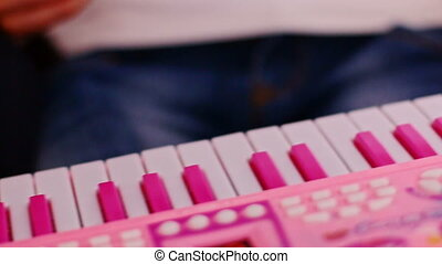 Macro Little Girl Finger Presses Keys on Pink Toy Piano