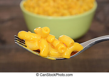 macro macaroni and cheese on a fork with green bowl in background
