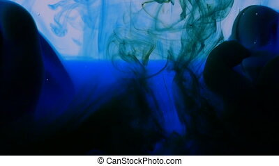 Macro of blue and green inks spreading in water looking like transparent colored veils abstract background