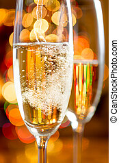 Macro of bubbles of Champagne against sparkling lights