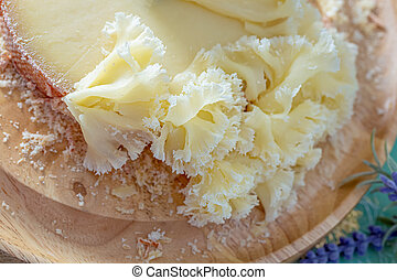 Macro of Cheese Monk Head. The texture of french cheese. Swiss cheese with crumbs on a wooden round surface. Top view.