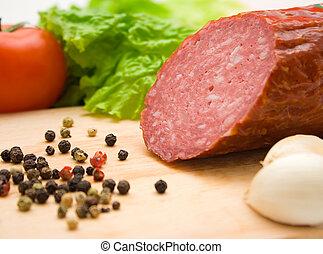 Macro of cut salami, pepper seeds and vegetables