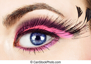 Macro of woman's eye with long pink feather fake eyelashes.