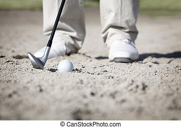 Macro of golfer in bunker.