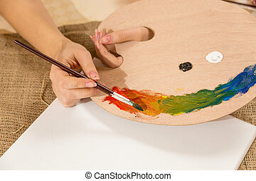 Macro photo of young female artist dipping paintbrush in paint