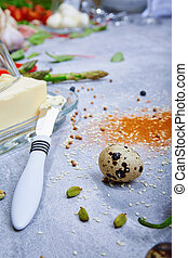 Macro picture of a glass container with butter next to a metal butter knife on a gray background. Cooking concept.