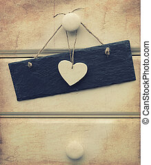 Macro retro cross processed effect image of heart and slate sign on wooden background