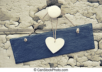 Macro retro cross processed effect image of wooden heart and slate sign on wooden background with flaking paint