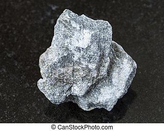 raw Soapstone stone ( talc - schist ) on dark - macro ...
