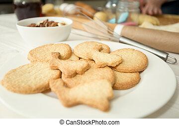 Macro shot of freshly baked cookies lying on white dish at kitchen