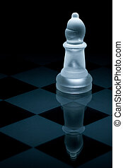 Macro shot of glass chess bishop against a black background