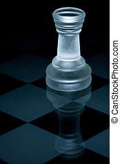 Macro shot of glass chess rook against a black background