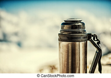 old shabby marching thermos in winter in snow