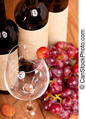 macro shot of one red grapes berry in glass. on wine bottle background