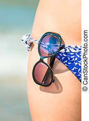 Macro shot of sunglasses on a swimsuit girl