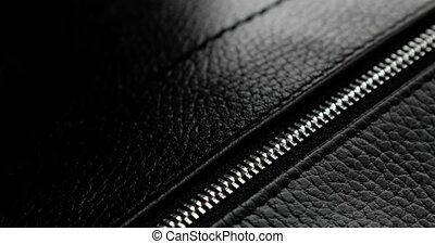 Testing metal zipper zips and unzips it on leather bag, man's hand closeup. Macro shot of unzipping and zipping metallic zipper on black leather accessory with guy's hand. Expensive brutal accessory.