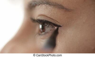 Macro shot of woman apply eyeliner
