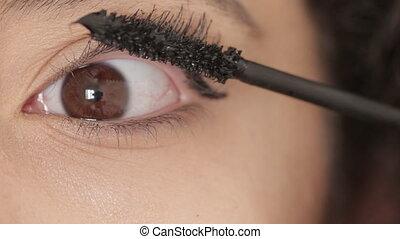Macro shot of woman enhance the eyelashes with lengthening...
