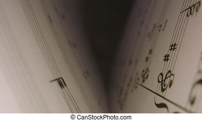 Macro shot through musical notes inside of book as it opens