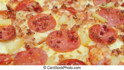 Macro slider shot of a pepperoni. bacon and pineapple pizza...