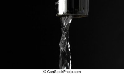 Macro slow motion shot of water running from tap against black background