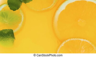 Macro slow motion video of orange slices and mint leaves in...