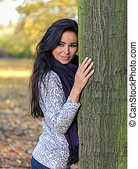 Smiling Pretty Young Woman Leaning on Tree Trunk